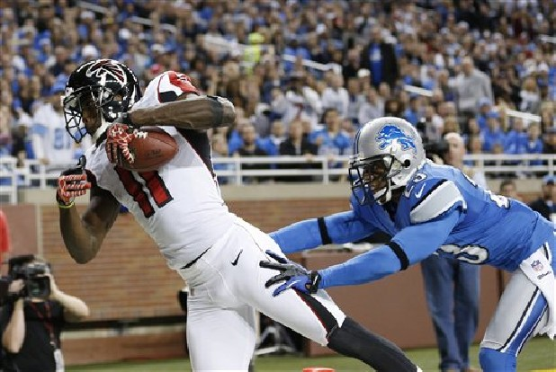 Atlanta Falcons wide receiver Julio Jones (11) falls into the end zone for a 16-yard touchdown as Detroit Lions cornerback Chris Houston defends duringan NFL  game at Ford Field in Detroit. In his second year with the Falcons, Jones says he's grateful to have a position coach so dedicated to his success.