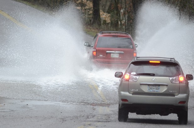 Vehicles drive through standing water Tuesday morning on Boy Scout Road as North Chickamauga Creek overflows its banks due to heavy rains.