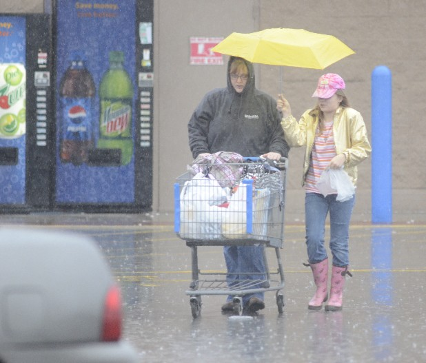 Lillias McManus holds an umbrella for her aunt, Jereann Hargis, as they make their way to their car through heavy rain at the Walmart in Kimball.