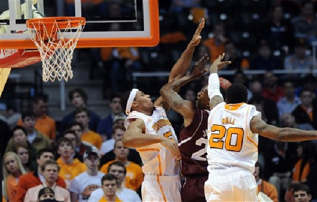 Tennessee forward Jarnell Stokes (5) and forward Kenny Hall (20) pressure Mississippi State forward Roquez Johnson (25) as he goes up for a basket Saturday during the first half of an NCAA  game at Thompson-Boling Arena in Knoxville.