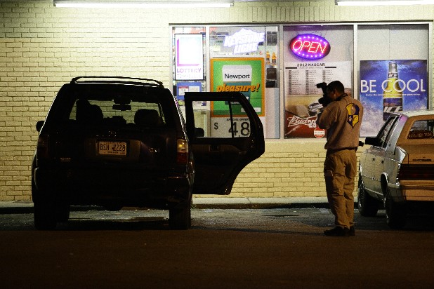 Police investigate the scene of a shooting Sunday night in the 3700 block of Rossville Boulevard. Three people were shot but police didn't believe their injuries were life-threatening.