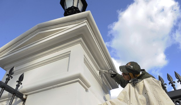 A painter touches up an entrance post outside the White House in Washington, D.C. on Friday in preparation for the inauguration of President Barack Obama.