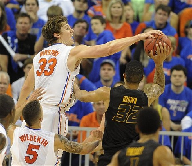 Florida's Erik Murphy (33) blocks Missouri guard Jabari Brown (32) as teammate Florida Gators guard Scottie Wilbekin (5) watches during the second half of an NCAA college basketball game in Gainesville, Fla.