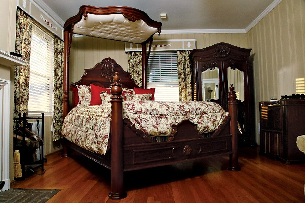 An 8-foot-tall, half-tester bed fills Danny Gilbert's master bedroom, complemented by an 8-foot antique armoire with beveled-glass doors. The half-canopy is tufted in cream damask.