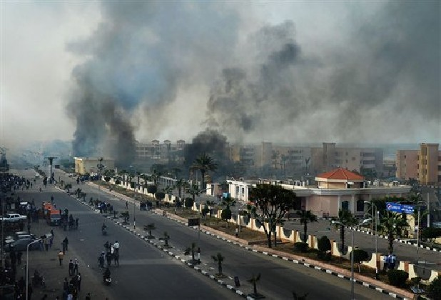 Smoke rises Sunday after Egyptian protesters clash with police, unseen, in Port Said, Egypt. Violence erupted briefly when some in the crowd fired guns and police responded with volleys of tear gas, witnesses said. State television reported 110 were injured. Egyptian health officials say 3 have been killed in clashes between protesters and police in Port Said.