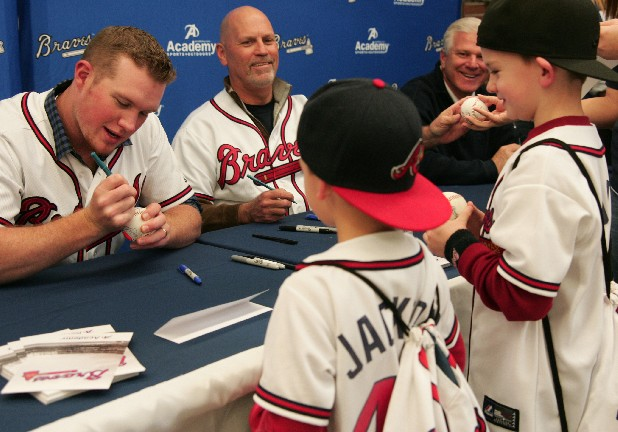 Jackson and Quentin Hawkins watch Atlanta Braves closer Craig Kimbrel autograph a baseball Monday at the Braves Country Caravan stop at the Academy Sports + Outdoors store on Shugart Road in Dalton.