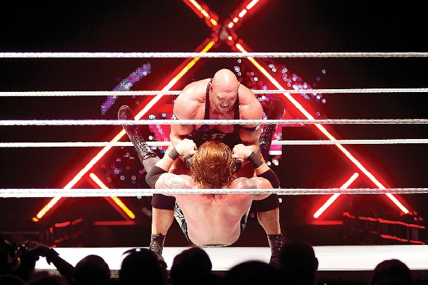 WWE wrestler, Ryback, slams his opponent, Heath Slater, onto the ring during a WWE Supershow match.