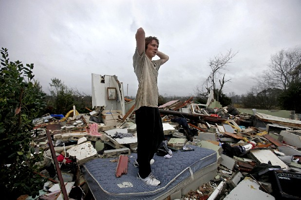 Will Carter, 15, surveys the damage to his house upon arriving home from school Wednesday following a tornado in Adairsville, Ga.