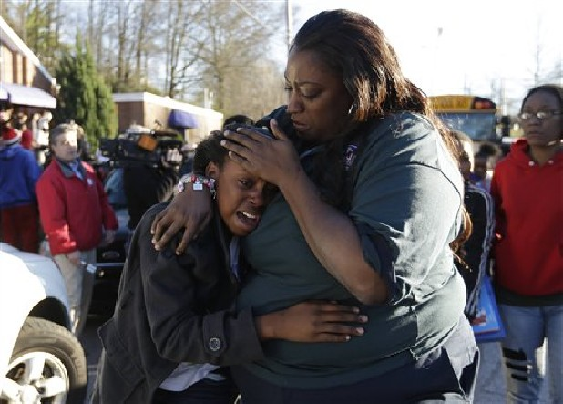 A woman comforts a child after after a shooting at an Price Middle school in Atlanta on Thursday. A 14-year-old boy was wounded outside the school Thursday afternoon and a fellow student was in custody as a suspect, authorities said. No other students were hurt.