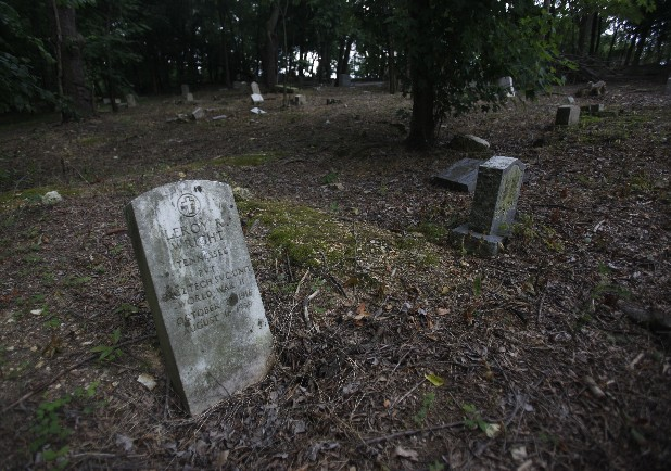 "The alleged headstone of Leroy Wright, the youngest of the ""Scottsboro Boys,"" leans heavily toward a semi-sunken grave at Pleasant Garden Cemetery in Chattanooga. The historically black cemetery has been seemingly neglected for decades, despite the occasional surge of community interest. David Young, a resident of the Ridgeside community whose home backs onto the cemetery property, has been fighting the underbrush and rampant foliage growth for three decades."