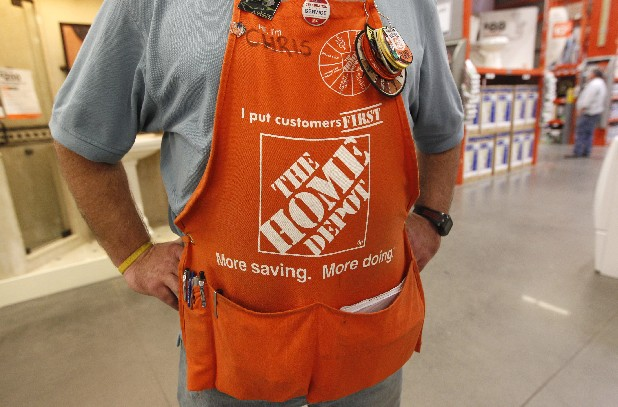 An employee wearing an apron stands in a Home Depot.