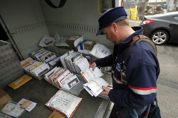Letter carrier Kevin Pownall gathers mail from the back of his truck in Philadelphia. The financially struggling U.S. Postal Service announced it will stop delivering mail on Saturdays but continue to deliver packages six days a week under a plan aimed at saving about $2 billion a year.
