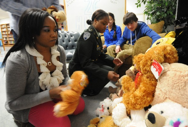 Gwendolyn Mynatt, left, and Keyanna Tatum add donated stuffed animals Thursday to more than 50 toys at Red Bank High. Student coucil president Matthew Smith, right, helped head-up the 26 Hugs project designated for kids at emergency scenes.