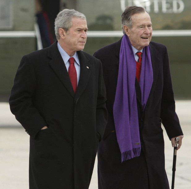President George W. Bush walks with his father, former President George H.W. Bush, at Andrews Air Force Base, Md. A criminal investigation is under way after a hacker apparently accessed private photos and emails sent between members of the Bush family, including both former presidents, according to reports Friday.