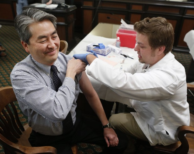 Assemblyman Al Muratsuchi, D-Torrance, reacts as he receives a flu shot from Tyler Poncy, a licensed vocational nurse during a free flu vaccine clinic at the Capitol in Sacramento, Calif. Health officials say the worst of the flu season appears to be over. The number of states reporting intense or widespread flu dropped again in late January 2013. The Centers for Disease Control and Prevention released the latest flu numbers on Friday.
