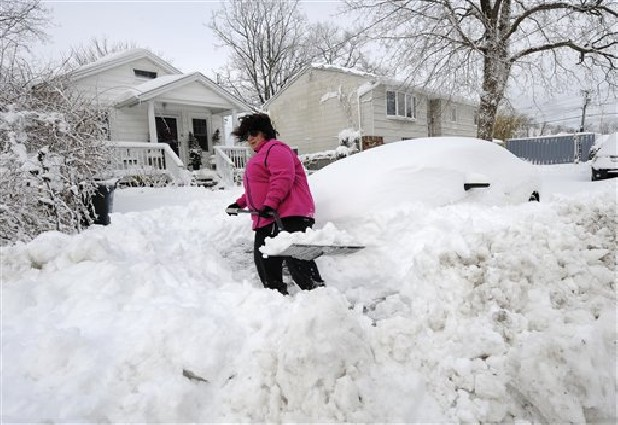 April Palmieri digs out her car in front of her home Saturday, background left, on 17th Street after a snow storm in Bayville, N.Y. Palmieri had five feet of water in her basement as result of the rains from Superstorm Sandy. A howling storm across the Northeast left the New York-to-Boston corridor shrouded in 1 to 3 feet of snow Saturday, stranding motorists on highways overnight and piling up drifts so high that some homeowners couldn't get their doors open. More than 650,000 homes and businesses were left without electricity.