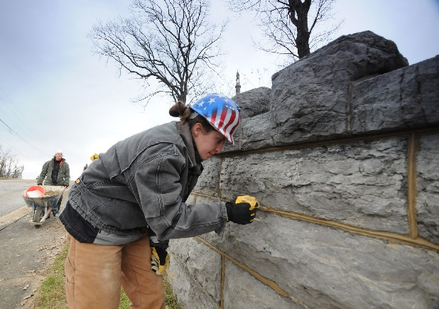 "Jessie Bender works to texture and seal the wall at Orchard Knob Reservation of the Chickamauga and Chattanooga National Military Park on Hawthorne Street near Highland Park on Tuesday. ""It is the first day for mortar,"" exhibit specialist Petey Bender said. Bender, far left, is site supervisor of the eight-man crew from the Historic Preservation Training Center in Frederick, Md."