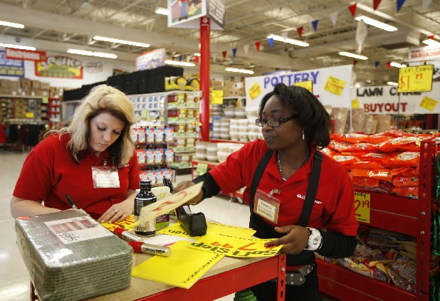 Lauren Ward, left, and Patience Olomu-Disi hand-write price cards Tuesday at Ollie's Bargain Outlet in Brainerd Village in preparation for the store's opening. Ollie's grand opening is Wednesday.