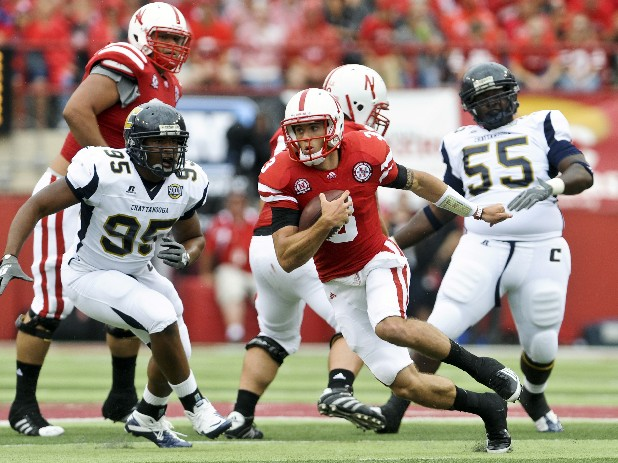 Nebraska quarterback Taylor Martinez carries the ball under pressure from Chattanooga's Wes Dothard (95) in 2011.