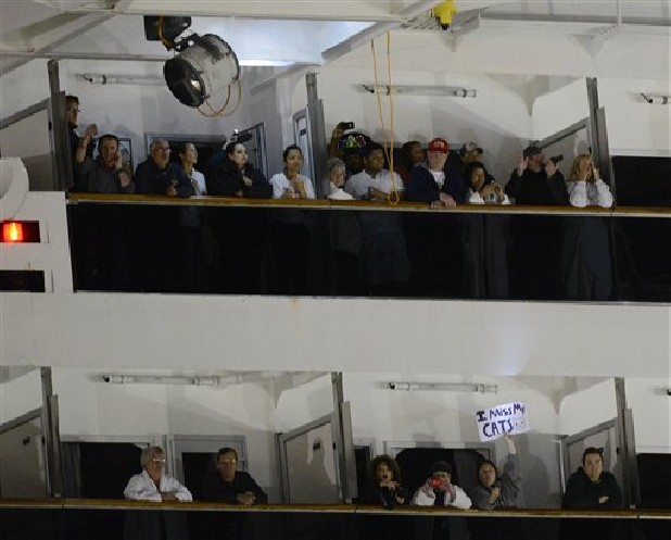 People watch from their balconies and hold up signs Thursday aboard the Carnival Triumph after it was towed to the cruise terminal in Mobile, Ala. The ship with more than 4,200 passengers and crew members has been idled for nearly a week in the Gulf of Mexico following an engine room fire.