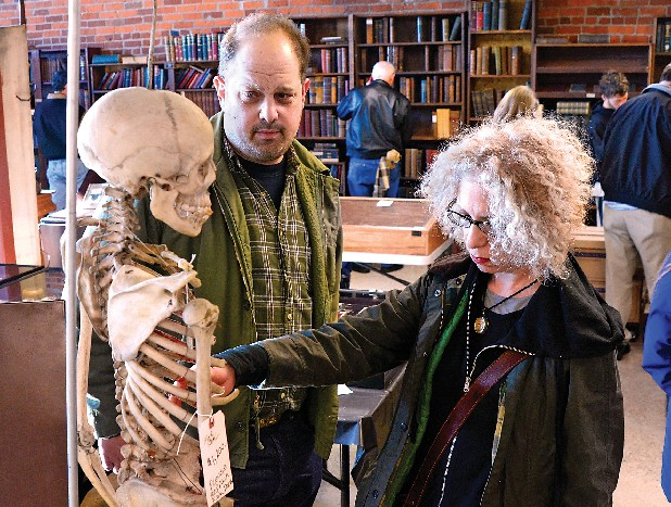 Mike Zohn, left, and Evan Michelson look at a skeleton at an estate sale of William Campbell's medical antiques Saturday on Chestnut Street. They are dealers from New York and specialize in medical equipment.