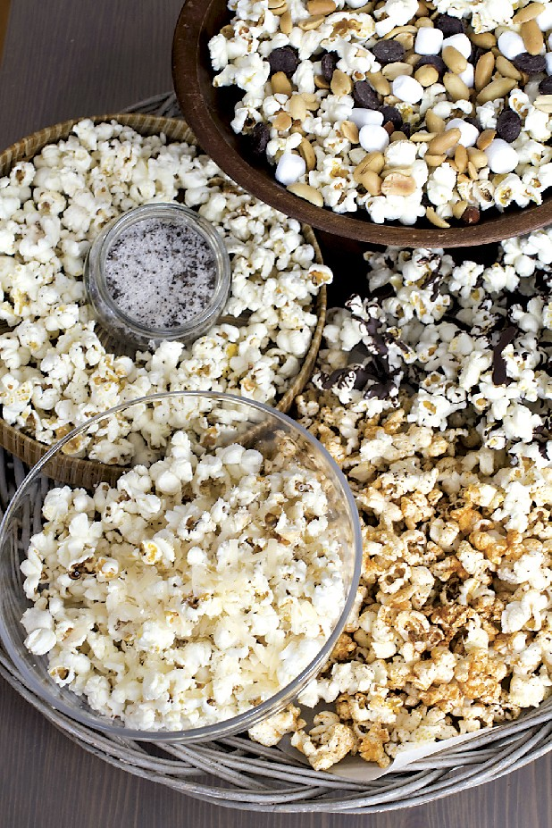 Topping possibilitites for stovetop popcorn include, from top clockwise, mini marshmallows, chocolate chips and salted peanuts, melted chocolate, sweet and spicy barbeque rub, or finely grated parmesan cheese and truffle salt.