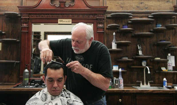 Barber Merrit Potter trims Ezequiel Garcia's hair at his barber shop on Dayton Boulevard. He has been cutting hair since 1962 and has recently expanded his White Oak Barber Shop to a second location on Lee Highway.