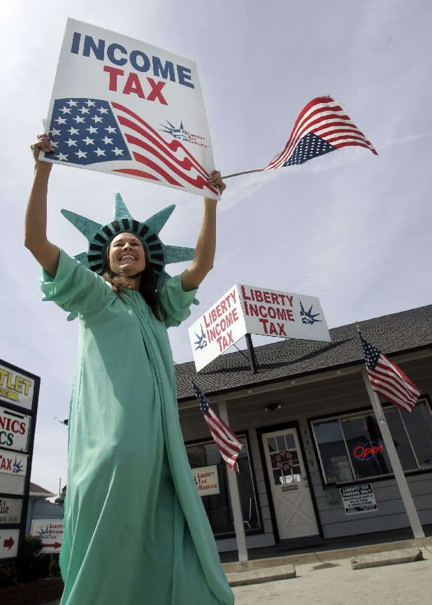 Julie Schaul, dressed like the Statue of Liberty, holds up an income tax sign to passing motorists in front Liberty Income Tax preparation services in Santa Cruz, Calif., in this file photo.