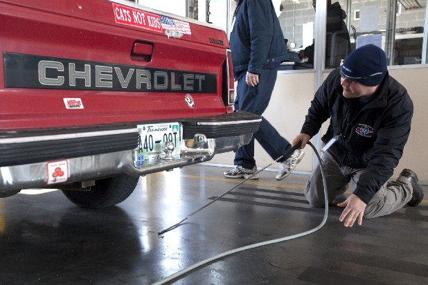 Emissions tester Mark Johnson searches for a tailpipe on a Chevrolet S10 truck Wednesday at the vehicle emissions testing facility on Riverfront Parkway in Chattanooga. The Tennessee Legislature is considering a bill that would exempt vehicles less than three years old from emissions tests.