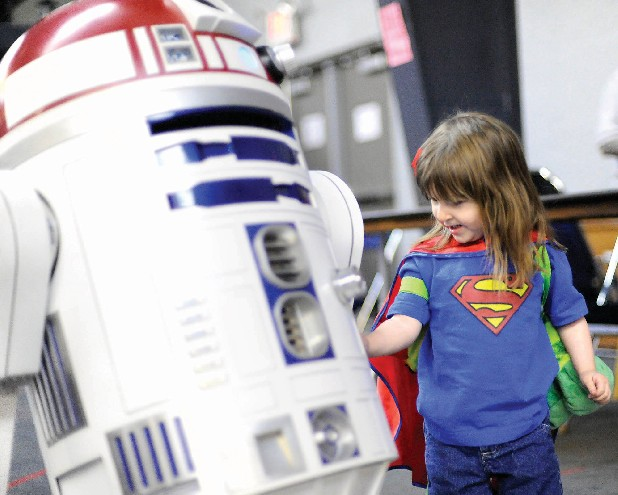 Dakota Faricelli inspects the Star Wars astromech droid, R3T2, at the 2012 Con Nooga convention.