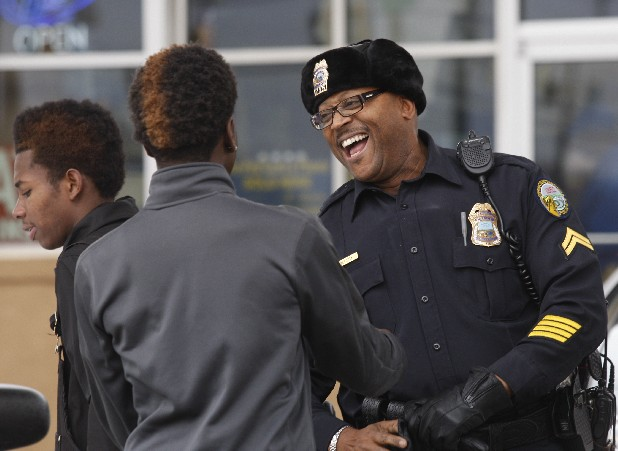 Chattanooga police officer Tetzel Tillery, right, talks with Kadarius Johnson, left, and Tycuan Vaughn outside a gas station on Fourth Avenue.