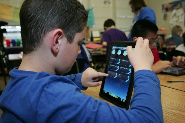 Garrett Payne uses an iPad at DuPont Elementary school Tuesday morning. The school has purchased dozens of iPads for use in their fourth- and fifth-grade classes to familiarize the students with the idea of using technology to find information.
