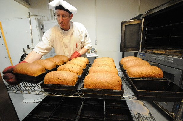 Sam Underwood removes freshly bakes loaves from the ovens at Clark's Bakery near Dunlap, Tenn.