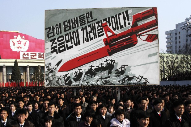 "North Koreans attend a rally to support a statement given on Tuesday by a spokesman for the Supreme Command of the Korean People's Army vowing to cancel the 1953 cease-fire that ended the Korean War at Kim Il Sung Square in Pyongyang, North Korea, on Thursday. North Korea on Thursday vowed to launch a pre-emptive nuclear strike against the United States. The billboard in background depicts a large bayonet pointing at U.S. army soldiers with writing reading ""If you dare invade, only death will be waiting for you!"""