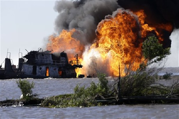 A fire still burns Wednesday after a tugboat and barge hit a gas pipeline yesterday evening in Perot Bay in Lafourche Parish, La.