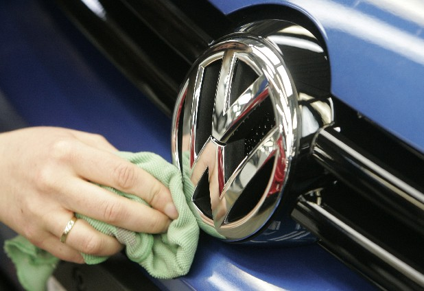 A worker cleans a Volkswagen logo in the production line at the Volkswagen plant in this file photo.