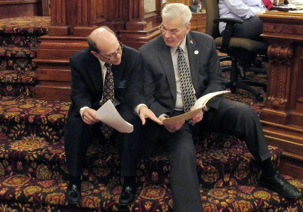 In this April 5, 2013, file photo Kansas state Reps. Steve Brunk, left, a Wichita Republican, and Arlen Siegfreid, right, an Olathe Republican, confer during a Statehouse debate in Topeka, Kan., prior to passage of the Second Amendment Protection Act.  Kansas Gov. Sam Brownback signed the bill later and became the first to sign a measure threatening felony charges against federal agents who enforce certain firearms laws on guns made and owned in his state.