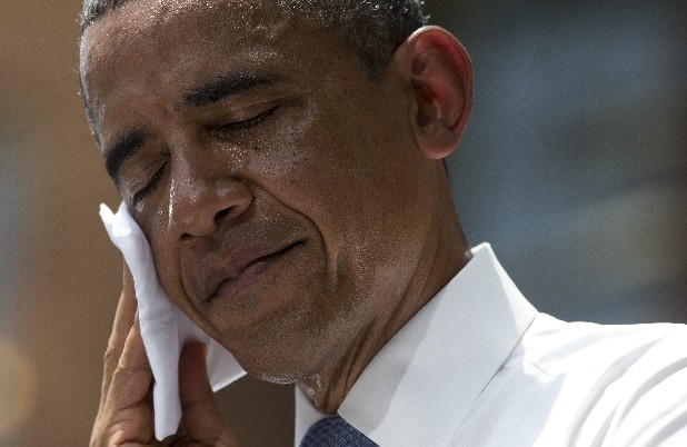 President Barack Obama wipes sweat from his head during a speech on climate change at Georgetown University in Washington.