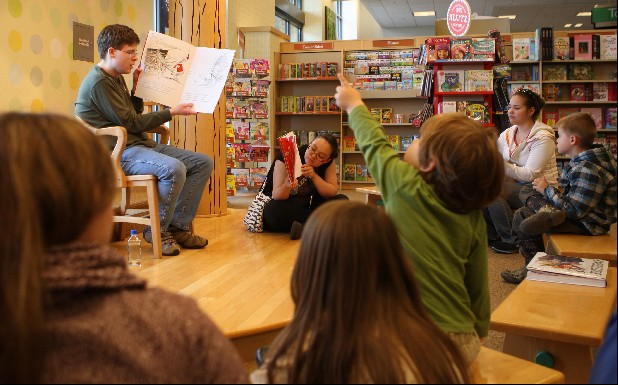"Sam Trapnell reads ""How the Grinch Stole Christmas,"" as Ann White holds a second book to show the illustrations, to children gathered at the Hamilton Place Barnes & Noble. He has been reading to kids since September."